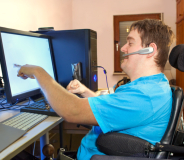 man with headset facing the computer monitor
