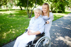 Girl pushing the wheelchair of an old woman